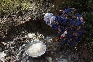 Mujer recogiendo agua de charco en Benin.
