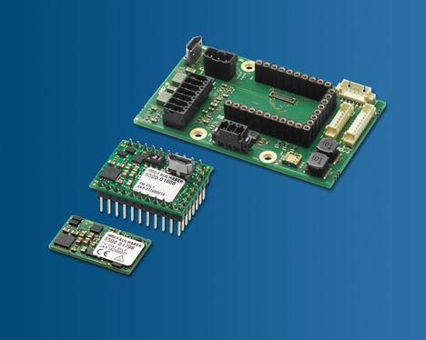 FAULHABER presenta dos nuevos controladores de movimiento: el MC3001B (primer plano) y el MC3001P (centro) que tienen en común su extrema miniaturización. Al fondo se muestra la placa base correspondiente del kit inicial.