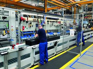 Las particiones entre los lugares de trabajo protegen a los empleados en el área de montaje.