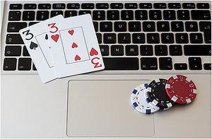 Online-Poker - Chips und Karten auf dem Notebook.