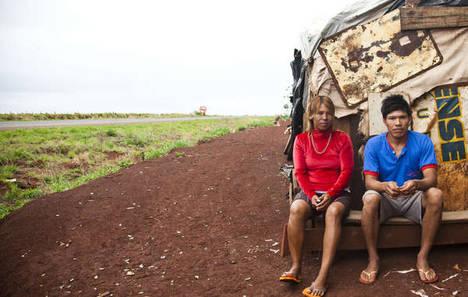 Una pareja guaraní-kaiowá sentada en la parte trasera de su alojamiento rodante, en la comunidad de Apy Ka'y, cerca de Dourados, mato Grosso do Sul, Brasil.